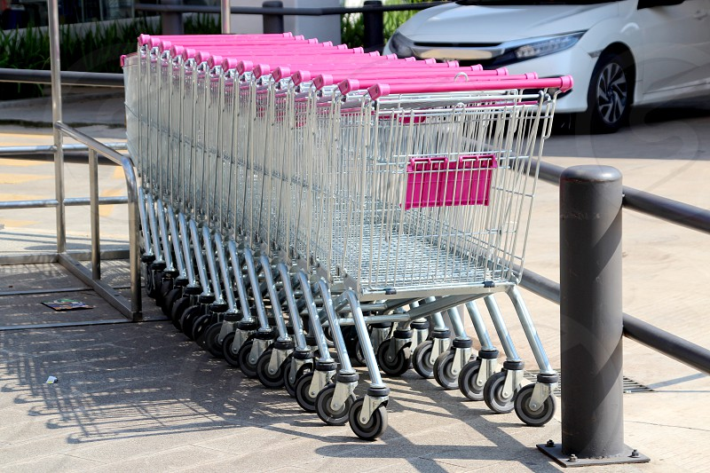 A row of supermarket trolleys with pink handles Phnom Penh Cambodia photo