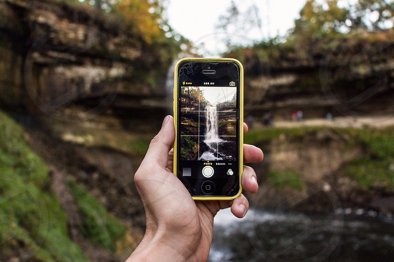 person capturing image of waterfalls using yellow iphone 5c photo