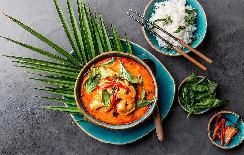 THAI SHRIMPS RED CURRY. Thailand tradition red curry soup with shrimps prawns and coconut milk. Panaeng Curry in blue plate on gray background. photo