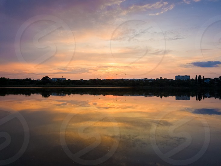Colorful sunset clouds symmetric reflected on the lake surface. Idyllic summer evening natural scene near a countryside pond with calm water. photo