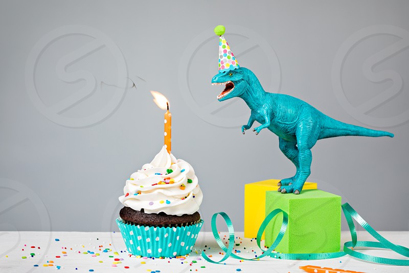 Toy Dinosaur blowing out a Birthday candle with cup cake on a gray background photo