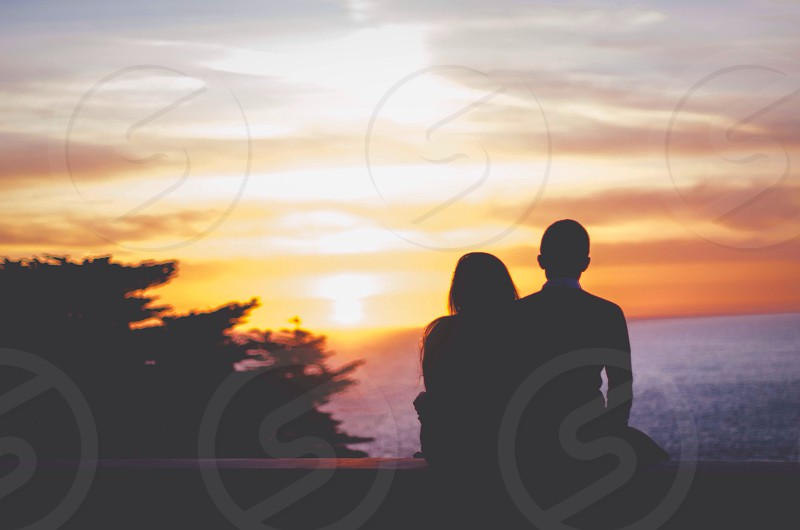 man and woman facing the sea silhouette  photo