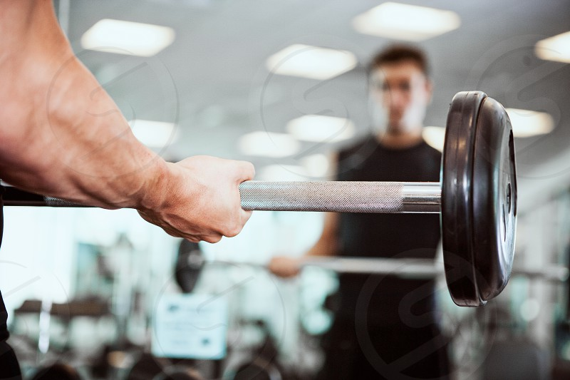 Man lifting barbell in gym.  barbell lifting weight training trainer man working out gym strong indoors exercise fitness photo