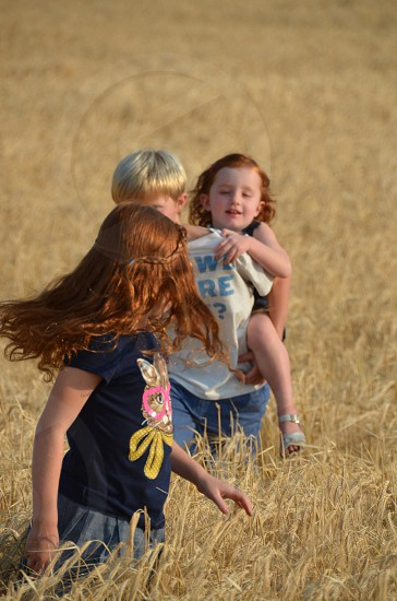 photo of boy carrying a girl over his shoulder while walking in brown grass fields photo