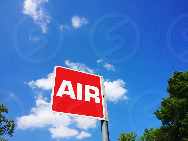 Red air sign against blue sky with clouds photo