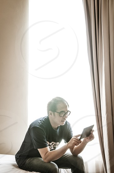 Casual adult male sitting on bed and working with tablet device in home office photo