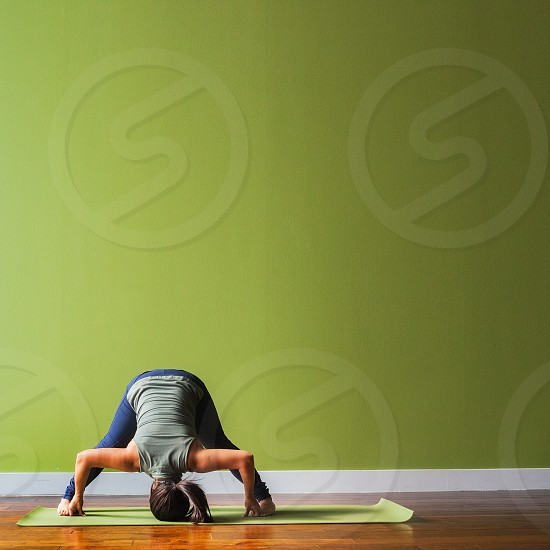 A young woman in a forward fold yoga position against a green background during the day. photo
