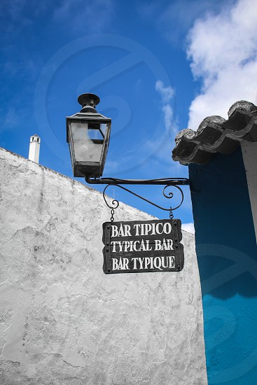 black metal street lamp by white concrete wall under blue sky with white clouds during daytime photo