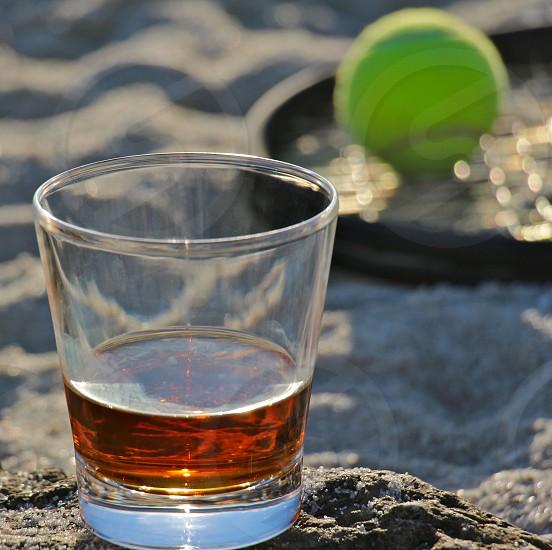 whiskey glass 1/4 full on a beach next to a tennis ball on a tennis racket photo