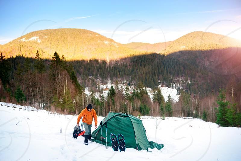 Man walking on snow near tent in winter photo