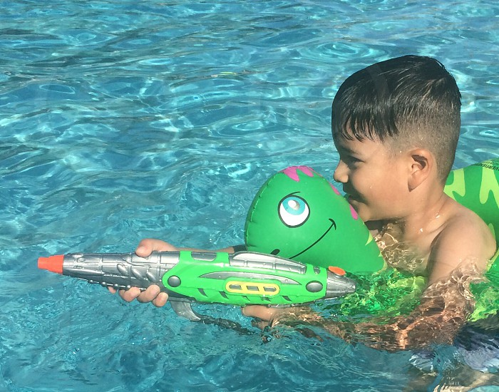 boy holding green and gray water gun on pool photo