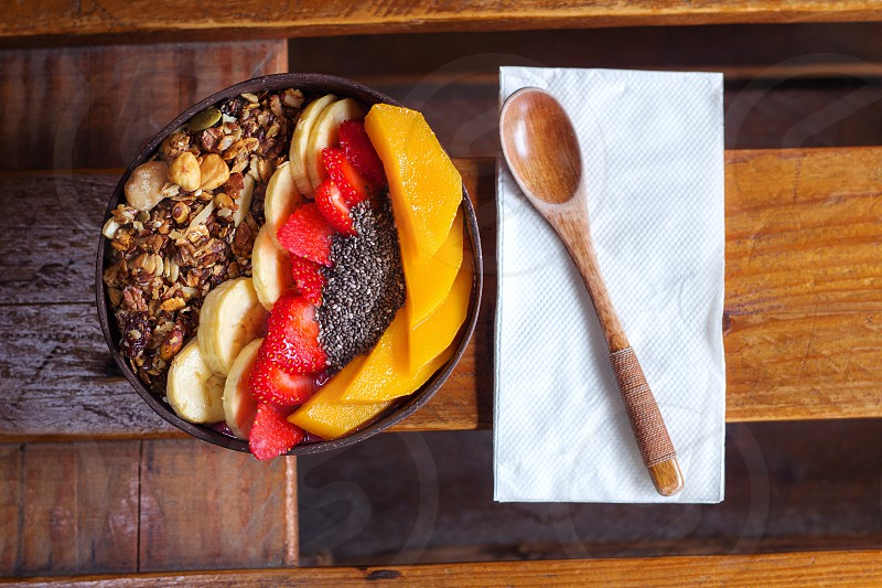 smoothie bowl for healthy breakfast. peach strawberry banana toasted muesli and chia seeds with berry base smoothie served on a wooden table with wooden soon top view. photo