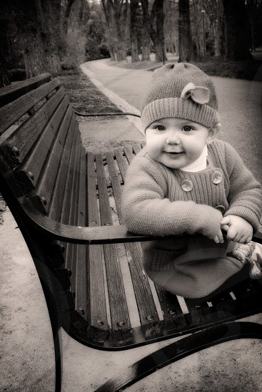 baby sitting on a wooden bench photo