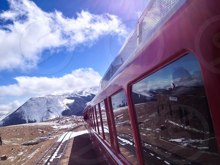 red train headed toward snow covered mountain photo