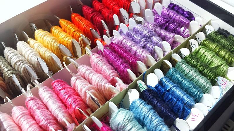 shades of pink spooled yarn beside shades of blue spooled yarn photo