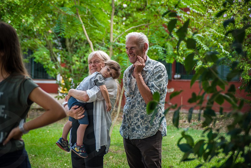 cool grandparents couple with toddler boy on grandmothers arms bonding and enjoying themselves photo