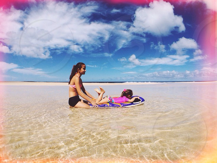 mother and daughter lying in shallow water on beach photo