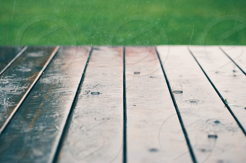 Closeup of wood planks while raining in perspective with grass at the top. Background of wooden natural surface and raindrops photo