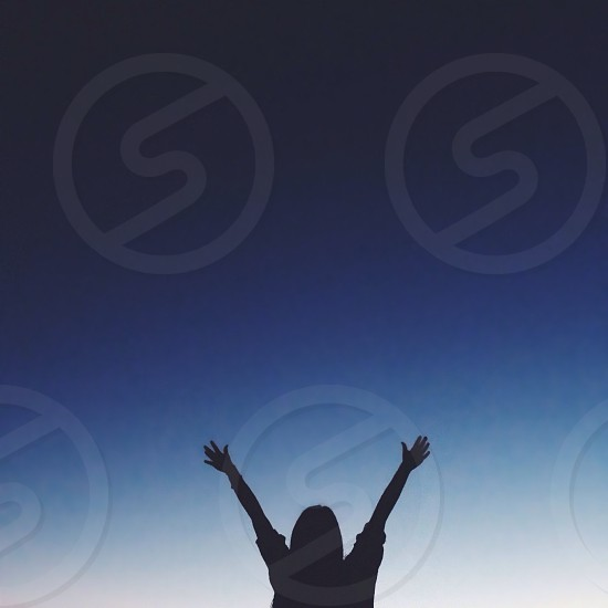woman raising her hands silhouette photo