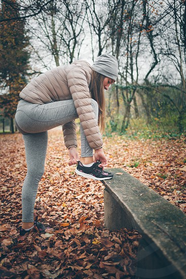 Young woman getting ready for jogging in the park photo
