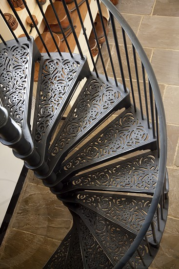 Iron spiral staircase going down into the kitchen photo