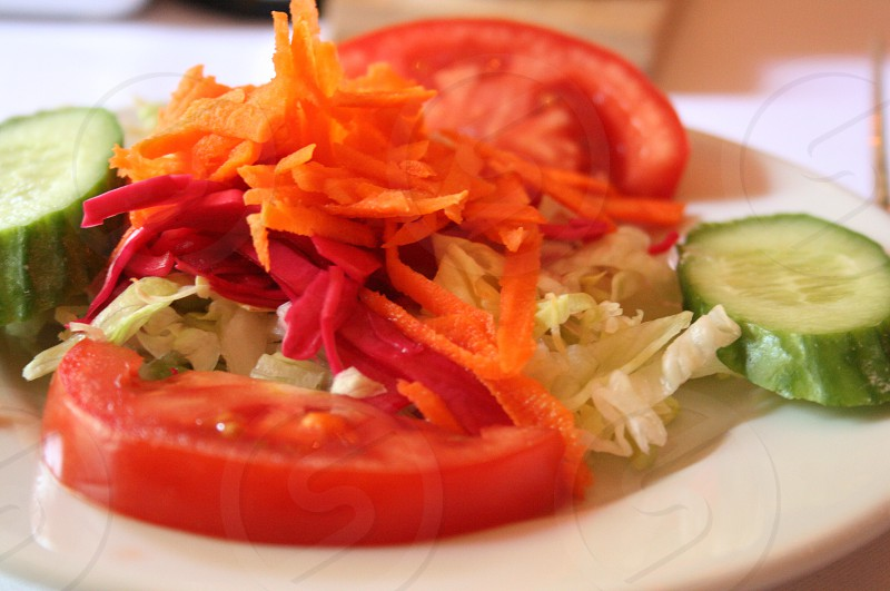 red sliced tomato and cucumber in white plate photo