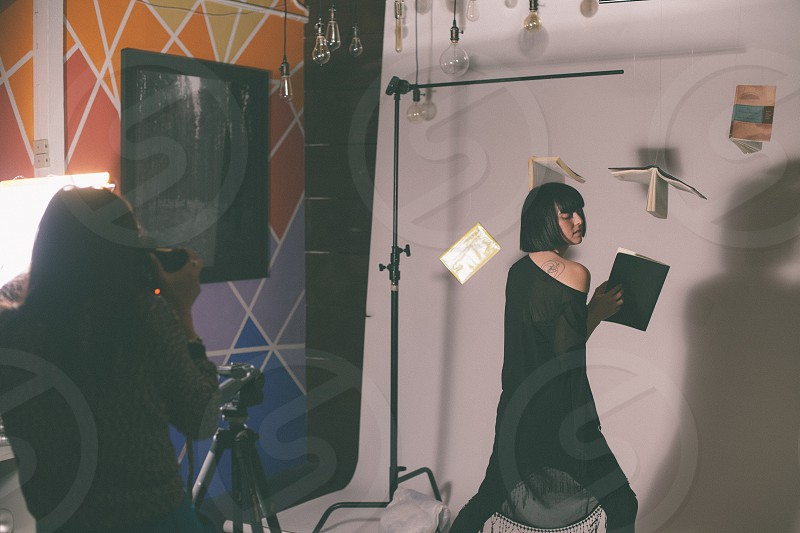 female model standing with books thrown on air in the studio photo