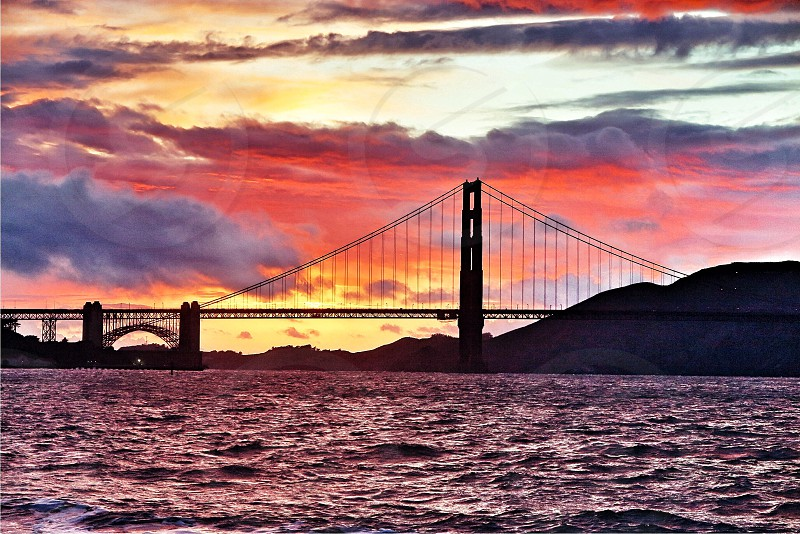 The beautiful dramatic and colorful sunset over the Golden Gate Bridge in San Francisco Ca during a storm.  photo