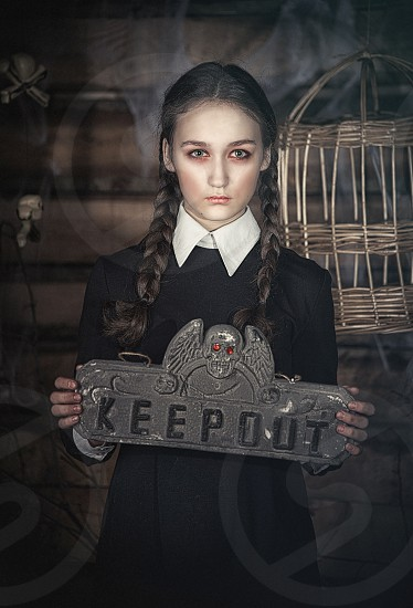 Girl in Halloween costume Anime with a sign in his hands adult make-up wide-open eyes photo