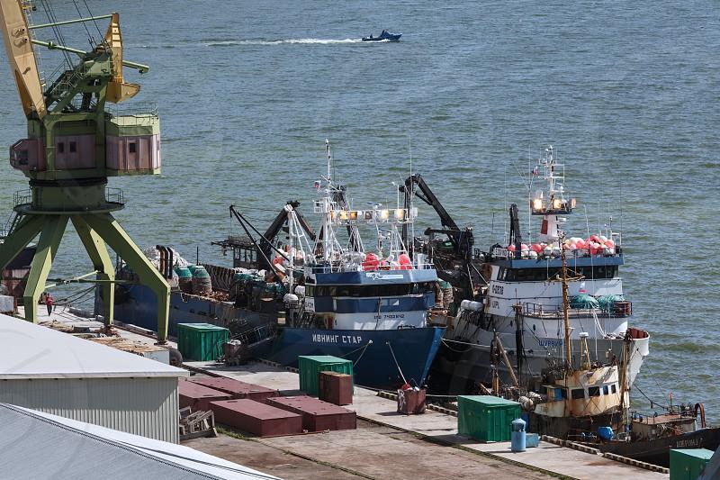 PETROPAVLOVSK-KAMCHATSKY KAMCHATKA RUSSIA - JULY 14 2013: Summer view of seaport Petropavlovsk-Kamchatsky and ships crabber standing at the pier. Russia Far East Kamchatka Peninsula Avacha Bay. photo