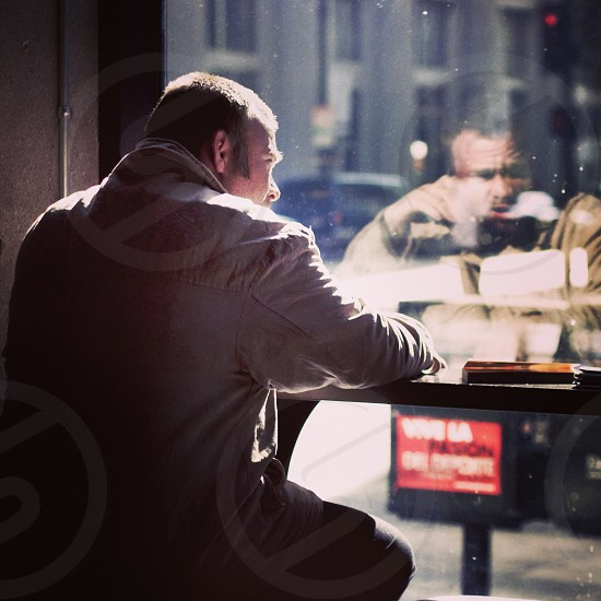 man looking out of cafe window photo