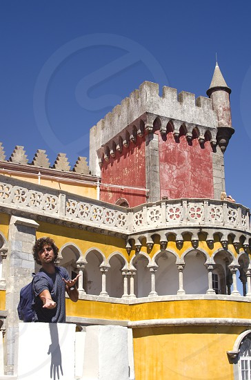 A boy simulating a romantic gentleman in one of the towers of the Pena palace in Sintra Portugal photo