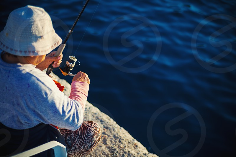 Older woman fishing with stick on sea dock.  photo