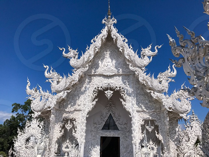 Outdoor day landscape horizontal colour Wat Rong Khun The White Temple Chiang Rai Thailand Thai Kingdom of Thailand travel tourism tourist wanderlust summer summertime temple Buddhist Buddhism spiritual pure holy dragon monster carved ornate elaborate art modern sculpture sculpted east eastern hands silver mirror mosaic magical mythical blue sky contrast photo