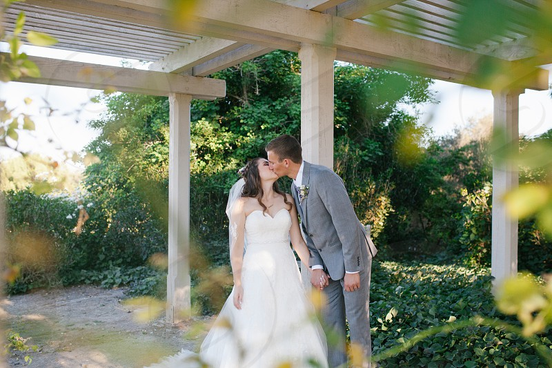 groom kissing his bride in white under a white pergolas photo