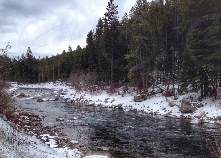 flowing river next to snow photo