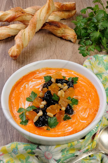 Sweet pumpkin puree soup with dried apricots prunes pine nuts photo