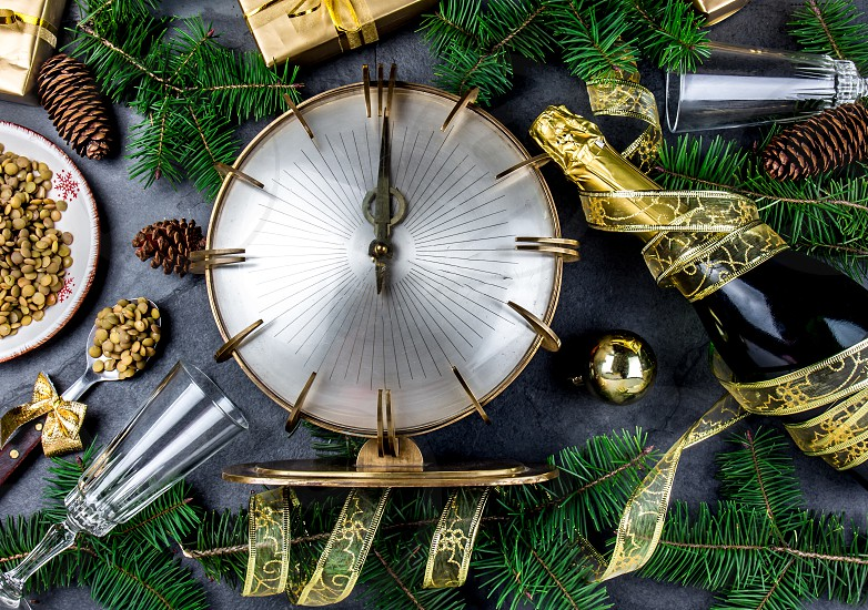 NEW YEARS EVE RITUAL. Eat spoon of lentil at midnigth. Holidey composition with vintage clock lentil and Christmas decorations. photo