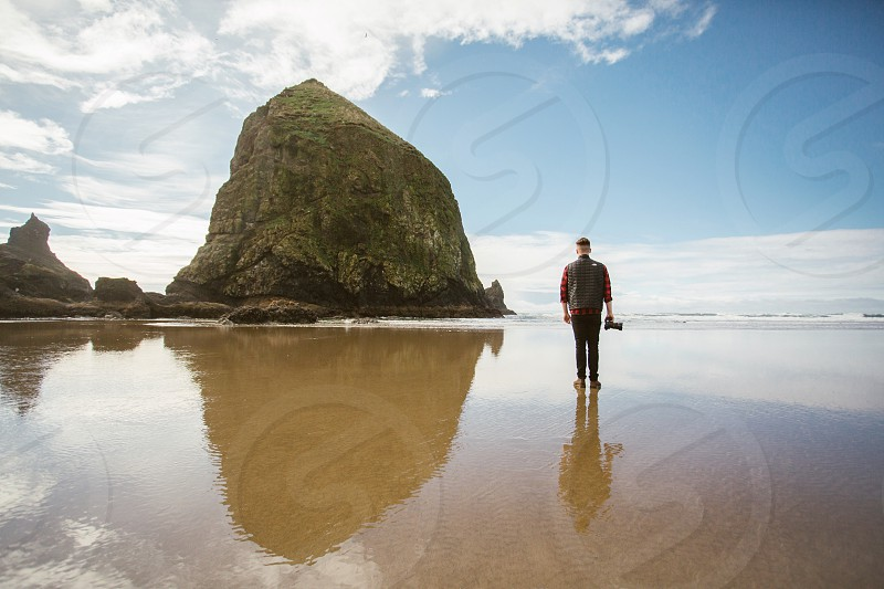 man in red and black checked shirt standing on seashore beside grey rock photo