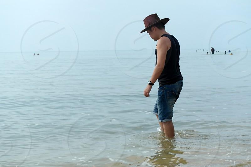 man wearing black tank top on sea during daytime photo