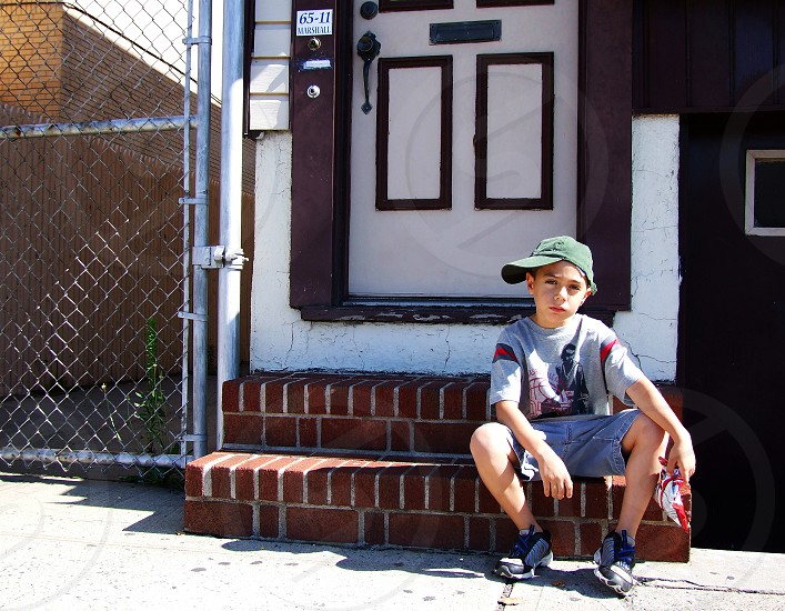'Street kid': A little boy with his cap visor turned  to the side sits on steps in in New York City. photo