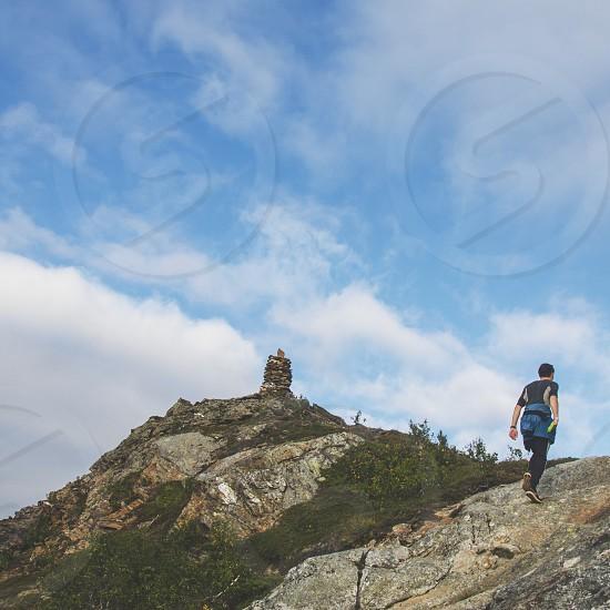 man hiking on rocky mountain photo