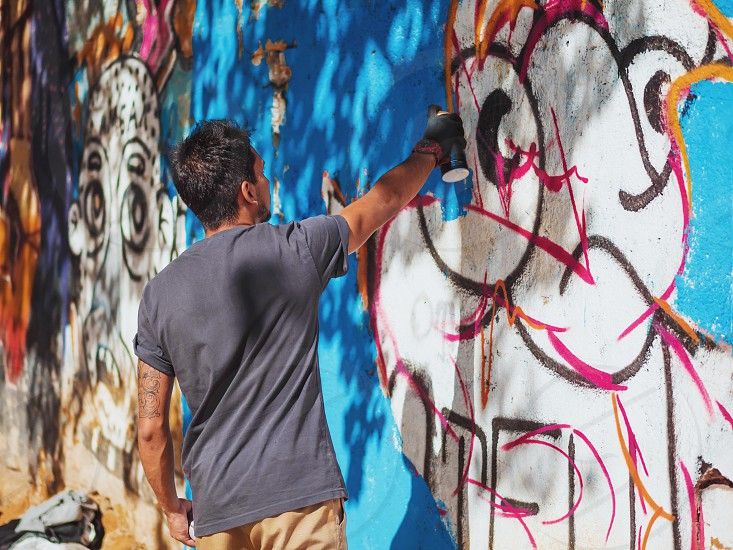 Creative art - teenage boy painting colorful abstract ornament graffiti on street wall with aerosol spray. Back view overall plan photo