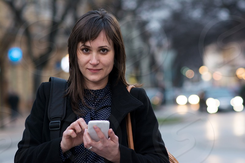 Young pretty woman browsing on her smartphone in the middle of the city center photo