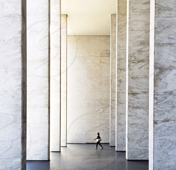 woman walking through marble columns photo