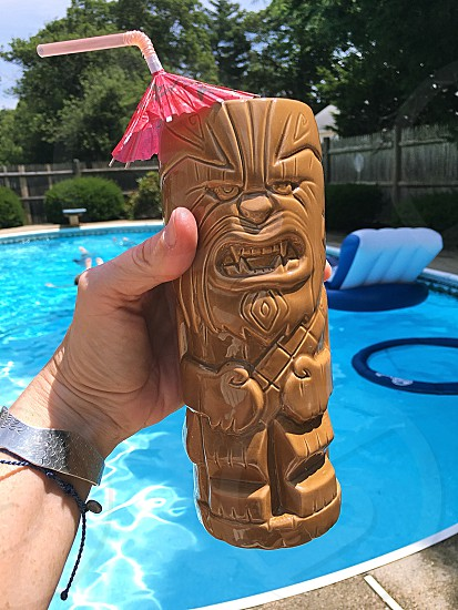 Tropical tiki party - this glass featured a tiki Chewbacca! Fun tiki glass Chewbacca Star Wars holding hand umbrella straw outside poolside  photo