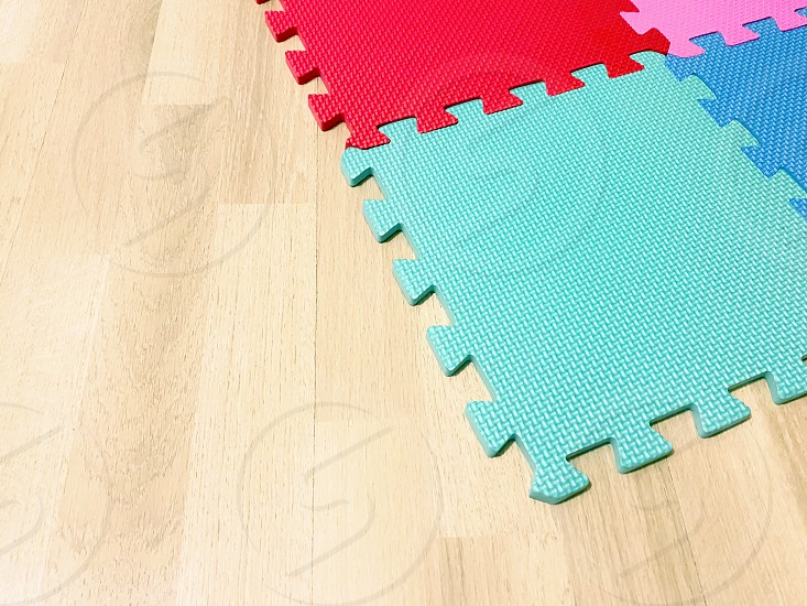Soft rubber mat composed of colored blocks intersected with each other on a wooden floor. Suitable for children to play or for yoga exercises. Interior shot photo