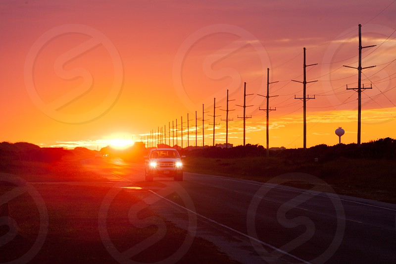Beautiful US Atlantic Coast sunset and car traffic on Highway 12 on Hatteras Island of Outer Banks OBX North Carolina NC US photo