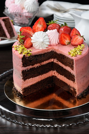 Chocolate strawberry cake decorated with berries meringue and pistachios in a cut photo