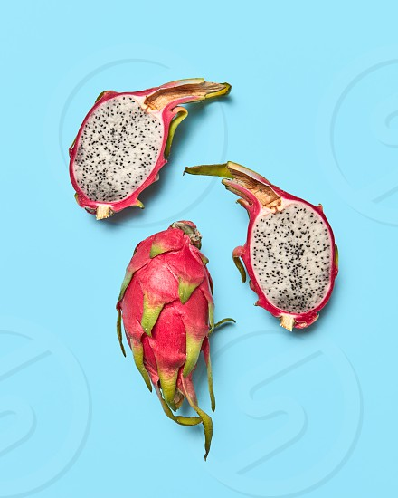 Exotic juicy fruit pitahaya. Whole and halved fruit on a blue background with space for text. Healthy food. Flat lay photo
